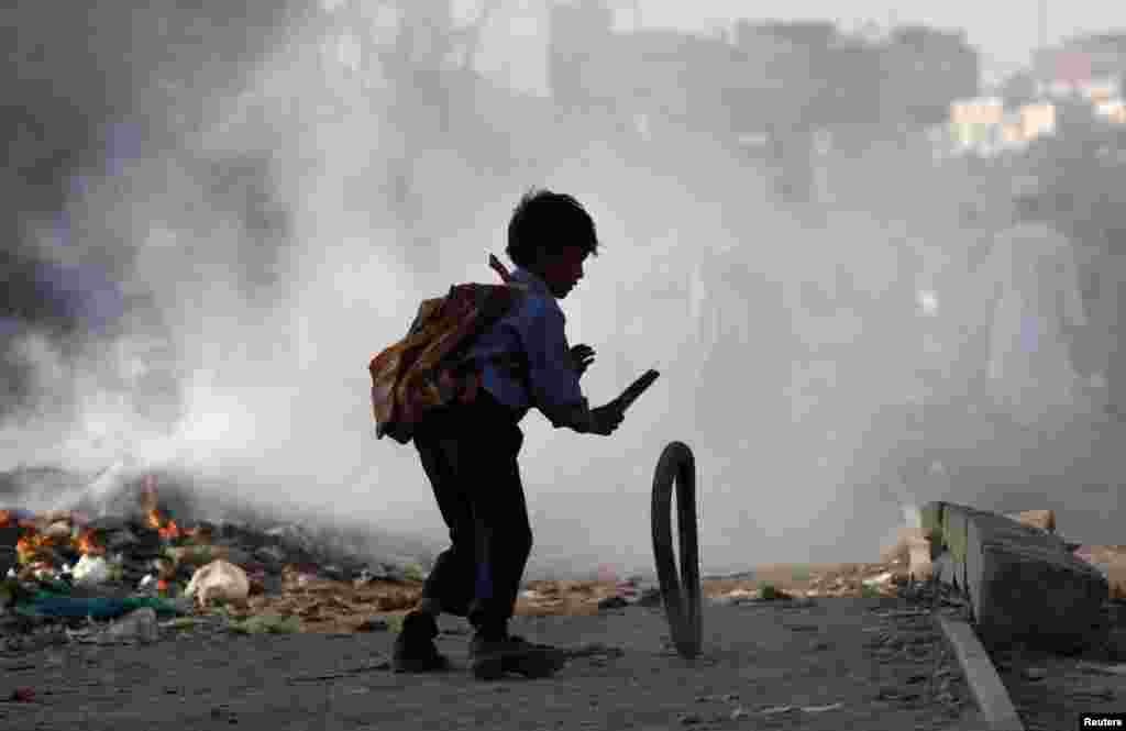 A boy plays with a tire near garbage being set on fire by residents of a slum in Karachi, Pakistan.