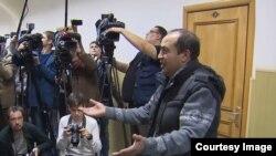 Ахрол Азимов уулдарынын сотунда журналисттерге интервью берүүдө.