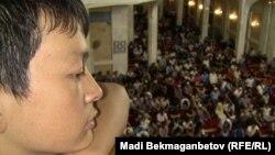 Молодой человек сверху смотрит на верующих в центральной мечети в Алматы. 15 августа 2012 года.