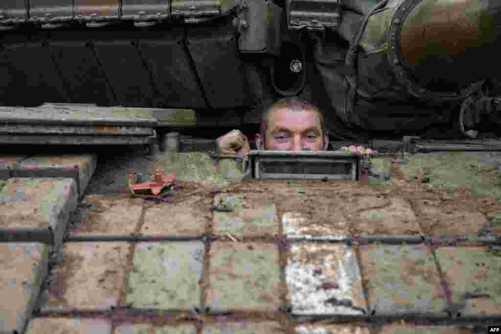 A Ukrainian serviceman looks out from a tank at a base near the village of Piskiy in eastern Ukraine's Donetsk region on February 16. (AFP/Oleksandr Ratushniak)
