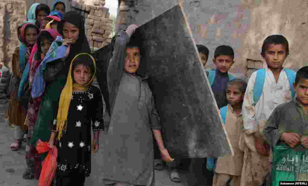 افغانستان: د جلال اباد ښار په څنډو کې افغان ماشومان د خپل ښوونځي ټولګي ته درومي.