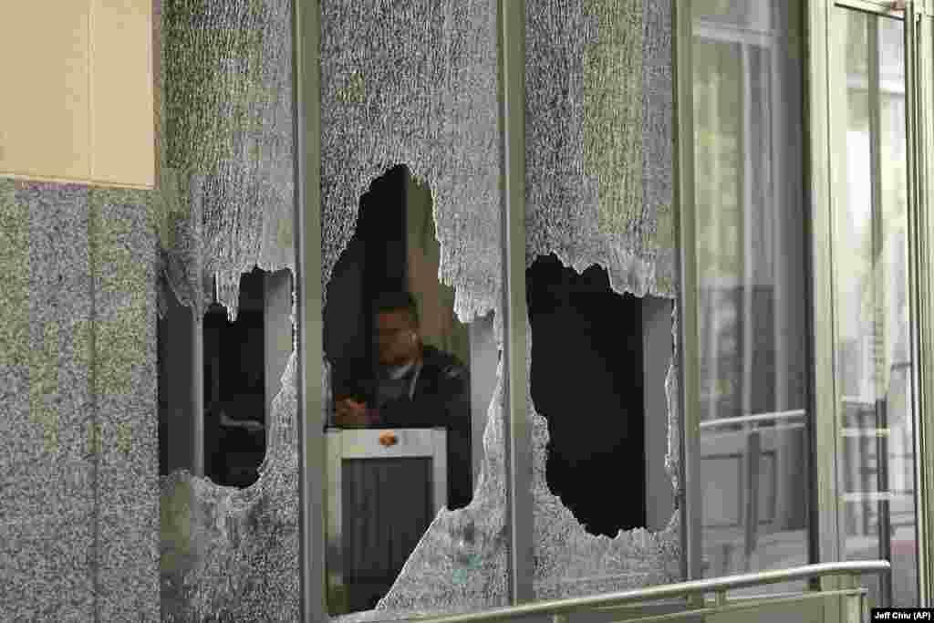 Чоловік сидить за розбитим вікном у федеральній будівлі Рональда В. Деллумса в Окленді, Каліфорнія. 26 липня 2020 року