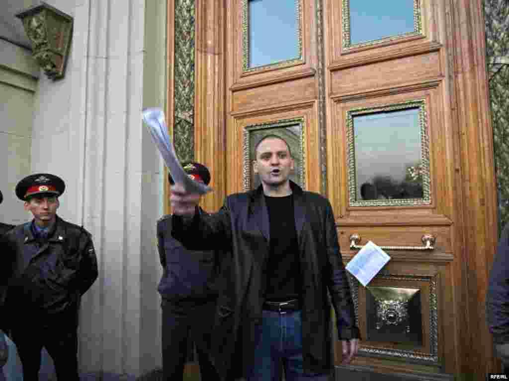 Лидер АКМ Сергей Удальцов оставляет резолюцию митинга на дверях мэрии