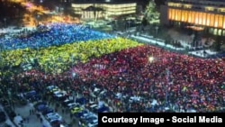 "Protesters held blue, yellow, and red placards representing the Romanian flag, shouting, ""Thou shalt not steal,"" ""A thief, two thieves, three thieves, all thieves,"" and ""Down with corruption."""