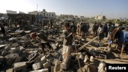 People gather at the site of an air strike in a residential area near Sanaa airport on March 26.