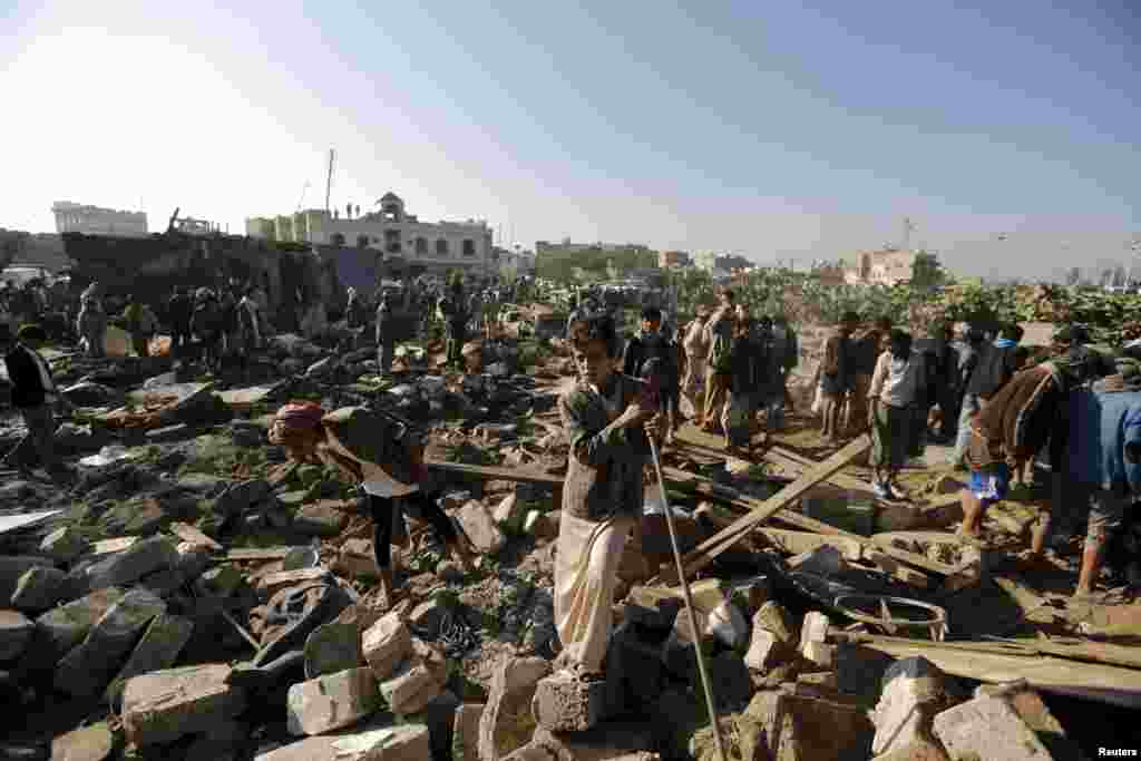 People gather at the site of an air strike on a residential area near Sanaa Airport in Yemen on March 26. (Reuters/​Khaled Abdullah)