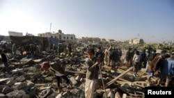 يمنيون يتفقدون موقع ضربة جوية قرب مطار صنعاء 26 اذار 2015