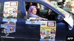 Женщина-агитатор в автомобиле с наклеянными на него предвыборными постерами, Аль-Ариш, 2 января 2012
