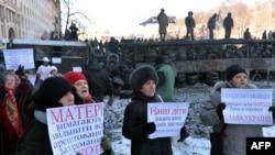 Аялдар полицияны кандуу эрегишти токтотууга жана протетчилерге кошулууга чакырган плакаттарды кармап турушат. Киев, 24-январь 2014