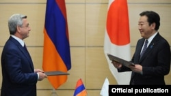 Japan - Prime Minister Yoshihiko Noda (R) and Armenian President Serzh Sarkisian exchange copies of a joint statement signed after their talks in Tokyo, 06Jun2012.