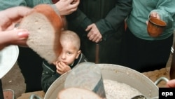 A boy stands among a line of people queuing for food at a charity distribution for poor people in Moscow.