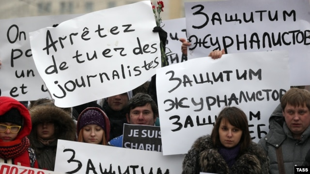 People hold placards as they pay tribute to the 12 people killed by two gunmen at the French weekly newspaper Charlie Hebdo's editorial office, outside French Embassy in Moscow on January 9.