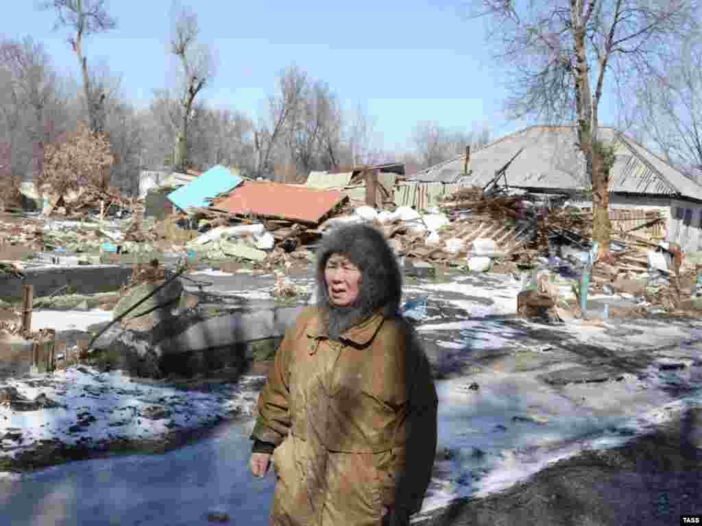 Қызылағаш тұрғыны су тасқыны салдарынан болған қирандылар жанында. Алматы облысының Ақсу ауданы, 14 наурыз 2010 жыл.