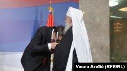 Српскиот претседател Александар Вучиќ му бакнува рака на владиката Иринеј