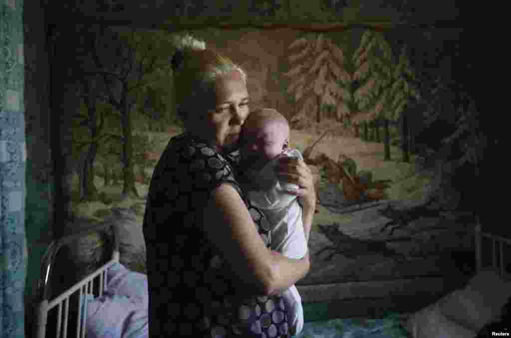 A mother and child who have fled from fighting in Slovyansk stand in their temporary accommodation in the eastern town of Nyzhnya Krynka on June 4.