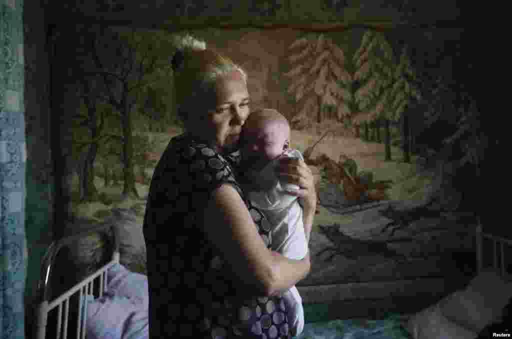 Женщина с ребенком, покинувшие Славянск, в центре временного размещения в городе Нижняя Крынка. 4 июня 2014 года.