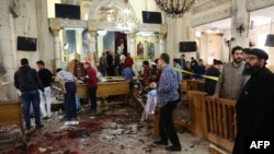 (WARNING: Graphic) People look at the aftermath following a bomb blast that struck worshipers gathering to celebrate Palm Sunday at the Mar Girgis Coptic Church in the Nile Delta city of Tanta, 120 kilometers north of Cairo, on April 9.