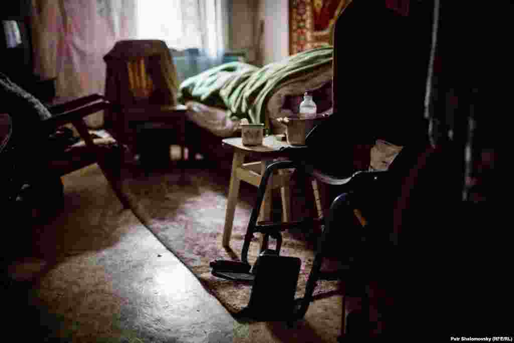 Maria, 81, lies in bed at her home. She cannot walk and is unable to leave the town, in spite of government efforts to help civilians flee.