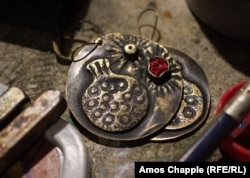 These pomegranate-themed earrings were fashioned from a bullet and autocannon ammunition.