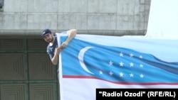 Дүйшөмбүдөгү тажик-өзбек концертине даярдыктын алкагында өзбек желеги илинип жаткан учур.