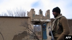 A soldier stands beside a damaged Taliban militant training center in Makeen, South Waziristan.