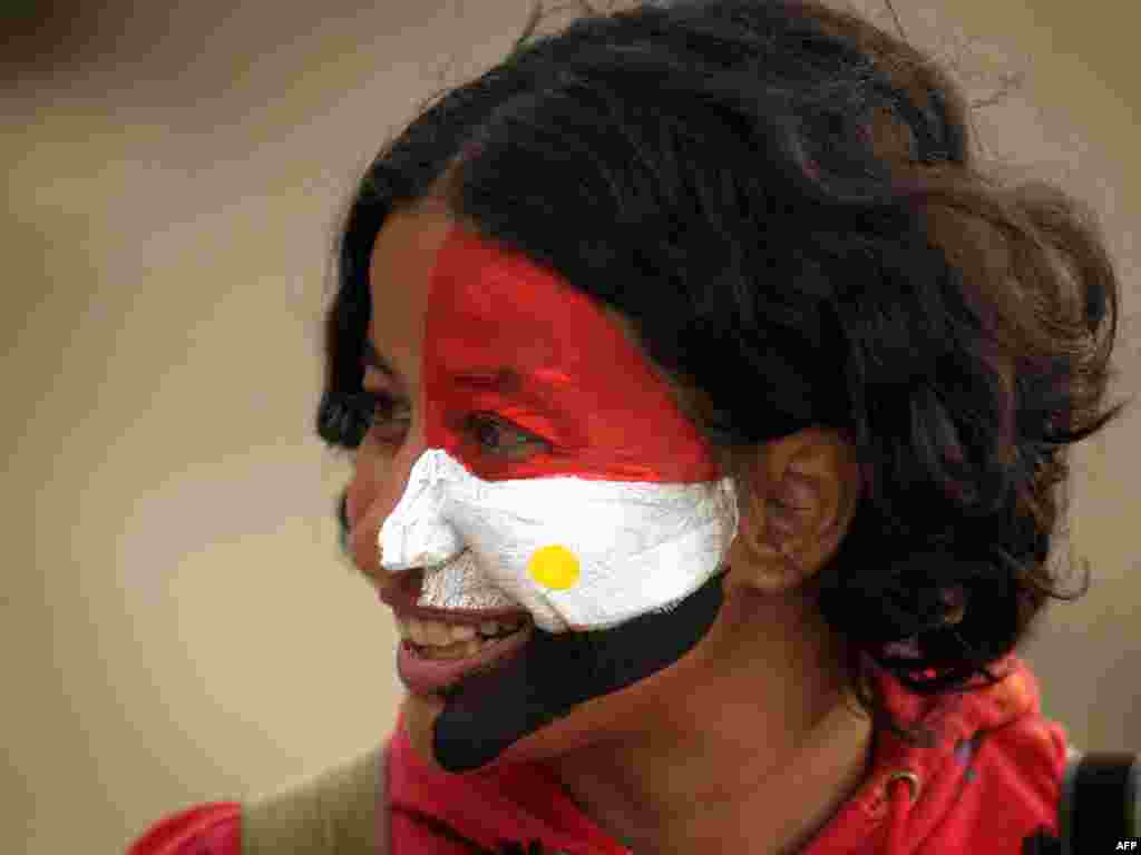 An antigovernment protester, her face painted in the colors of the national flag, stands in Tahrir Square on February 4.