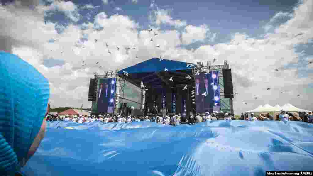 Голуби злітають над сценою й великим прапором після промови Сергія Аксьонова
