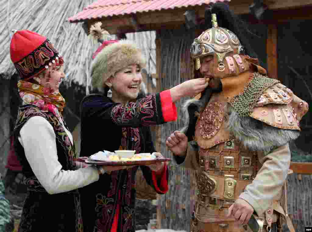 A woman dressed in national costume offers traditional local dishes during Norouz celebrations in Bishkek. (epa/Igor Kovalenko)