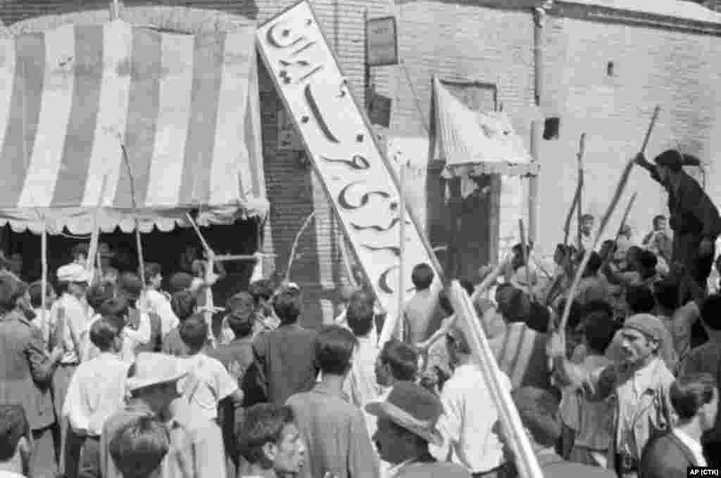 A crowd of demonstrators tears down the sign of the Iran Party, part of Mossadegh's National Front, at its headquarters on August 19.