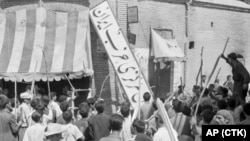 A crowd of demonstrators tear down the Iran Party's sign from the front of the headquarters in Tehran on August 19, 1953, during the pre-Shah riot that swept through the capital and ousted Prime Minister Mohammad Mossadegh.