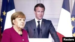 د عکس ښي لور ته د فرانسې ولسمشر ایمانول مکرون او چپ طرف ته د جرمني صدراعظمه انګېلامېرکل