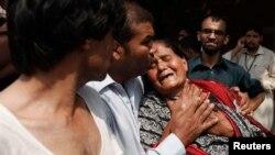 Hristian bir aýal partlamada ölen oglunyň gymyny çekýär. Peşewar, Pakistan. 22-nji sentýabr, 2013 ý.