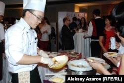 Официант раздает гостям блины с яблоками по-французски. Алматы, 21 ноября 2014 года.