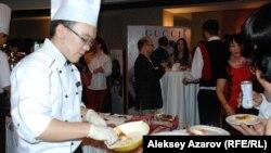 Кельнер обслуживает гостей мероприятия Божоле Нуво. Алматы, 21 ноября 2014 года.