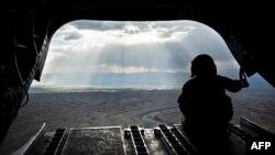 """Американский солдат смотрит на горы афганской провинции Логар из вертолета """"Чинук"""", май 2014 года"""