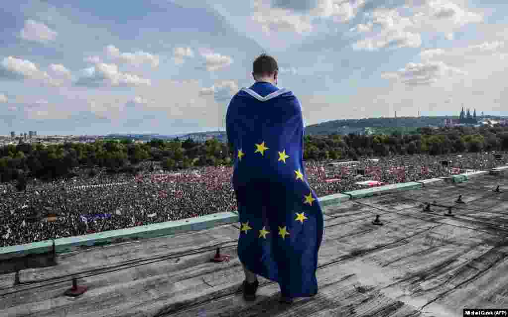 A man wrapped in a European flag observes a monster rally demanding the resignation of Czech Prime Minister Andrej Babis in Prague on June 23.