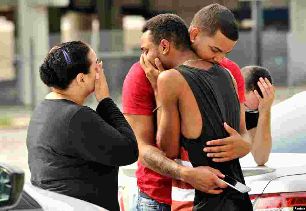 Friends and family members embrace outside Orlando police headquarters following the June 12 massacre at the Pulse nightclub, where 49 people were shot and killed by Omar Mateen, a U.S.-born citizen of Afghan descent. Police said the attacker opened fire with an AR-15 assault rifle and a handgun in the nightclub shortly before 2 a.m. and then held a group of club patrons hostage for three hours before he was killed in a shoot-out. (Reuters/Steve Nesius)
