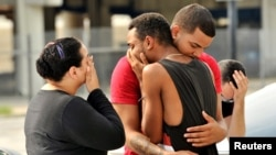 Friends and family members embrace outside Orlando Police Headquarters after a mass shooting at the Pulse night club.