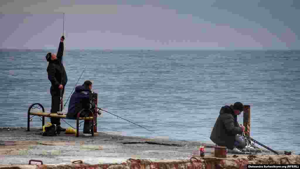 Местные рыбаки на пирсе пляжа «Русалка»