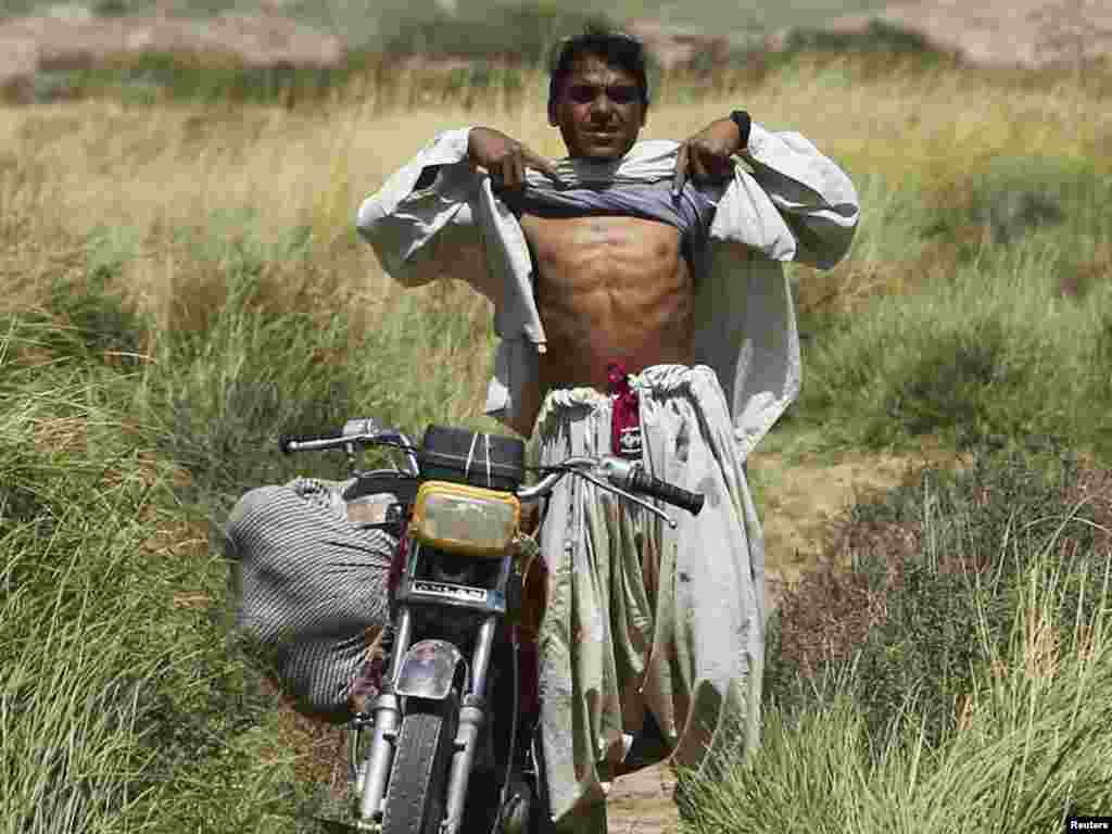 An Afghan villager raises his shirt to show that he is not wearing a suicide bomb vest to U.S. Marines from the 1st Light Armored Reconnaisance Battalion patrolling an area in Taghaz village in Helmand Province on September 9. Photo by Erik de Castro for Reuters