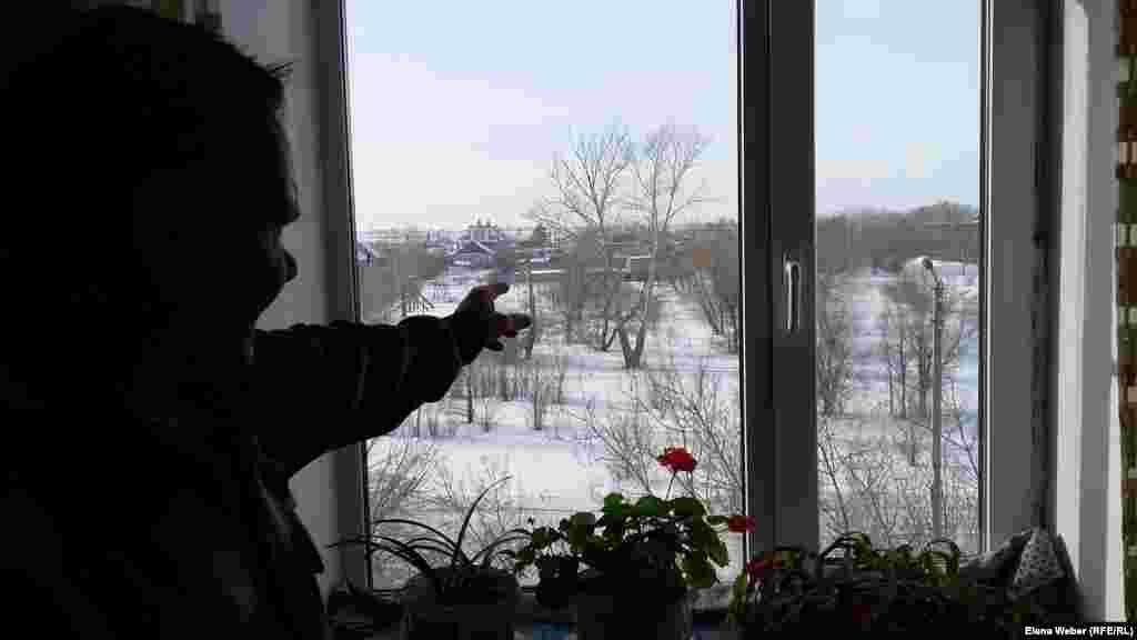 Житель поселка Шахан Олег Осипов из окна своей квартиры показывает место, где в начале 2000-х годов был взорван дом в целях его утилизации. По мнению Олега, из-за этого пострадали близлежащие дома, в том числе и тот, в котором живет он сам. Карагандинская область, 10 января 2017 года.