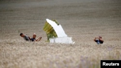 Malaysian air-crash investigators take photos of the crash site of Flight MH17 on July 22.