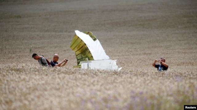 Malaysian air-crash investigators take photos of the crash site of Flight MH17 on July 22.