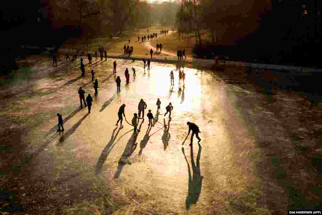 The sun sets as people play on a frozen pond and walk along the paths of a park in Berlin. (AFP/Odd Anderson)
