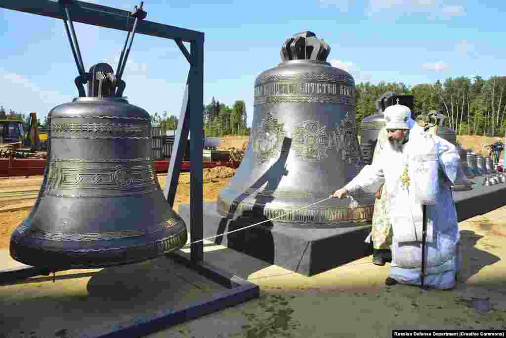 Some of the bells that have since been installed in the church belfry being tested by a priest in August 2019. The largest bell (center) weighs around 10 tons.