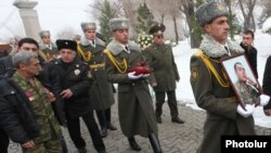 Armenia - An honor guard holds the picture of Sergeant Armen Hovannisian during his state funeral in Yerevan's Yerablur military cemetery, 22Jan2014.