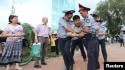 Law enforcement officers detain a man during an opposition protest in Almaty.