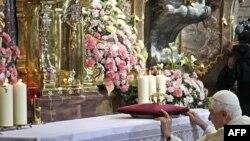 "Pope Benedict kneels before the ""Infant Jesus of Prague"" on September 26."