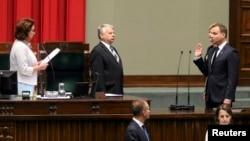 Польшанын быйыл шайланган президенти Анжей Дуданын (колун көтөрүп жаткан) кызматка киришүү аземи. Ошондой эле парламенттин жана сенаттын төрагалары. 6-август, 2015-жыл