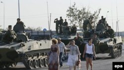 Civilians walk past Russian armored vehicles with servicemen atop on a road outside the town of Kamensk-Shakhtinsky in Rostov region, about 30 km from the Russian-Ukrainian border, August 15, 2014